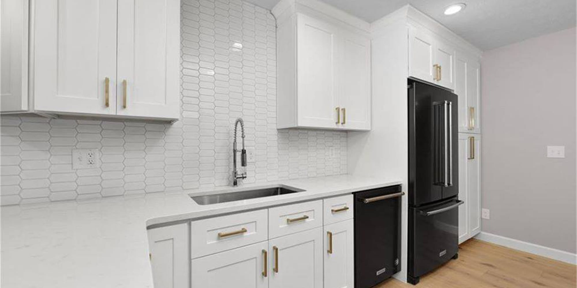white kitchen with black dishwasher and fridge and silver sink