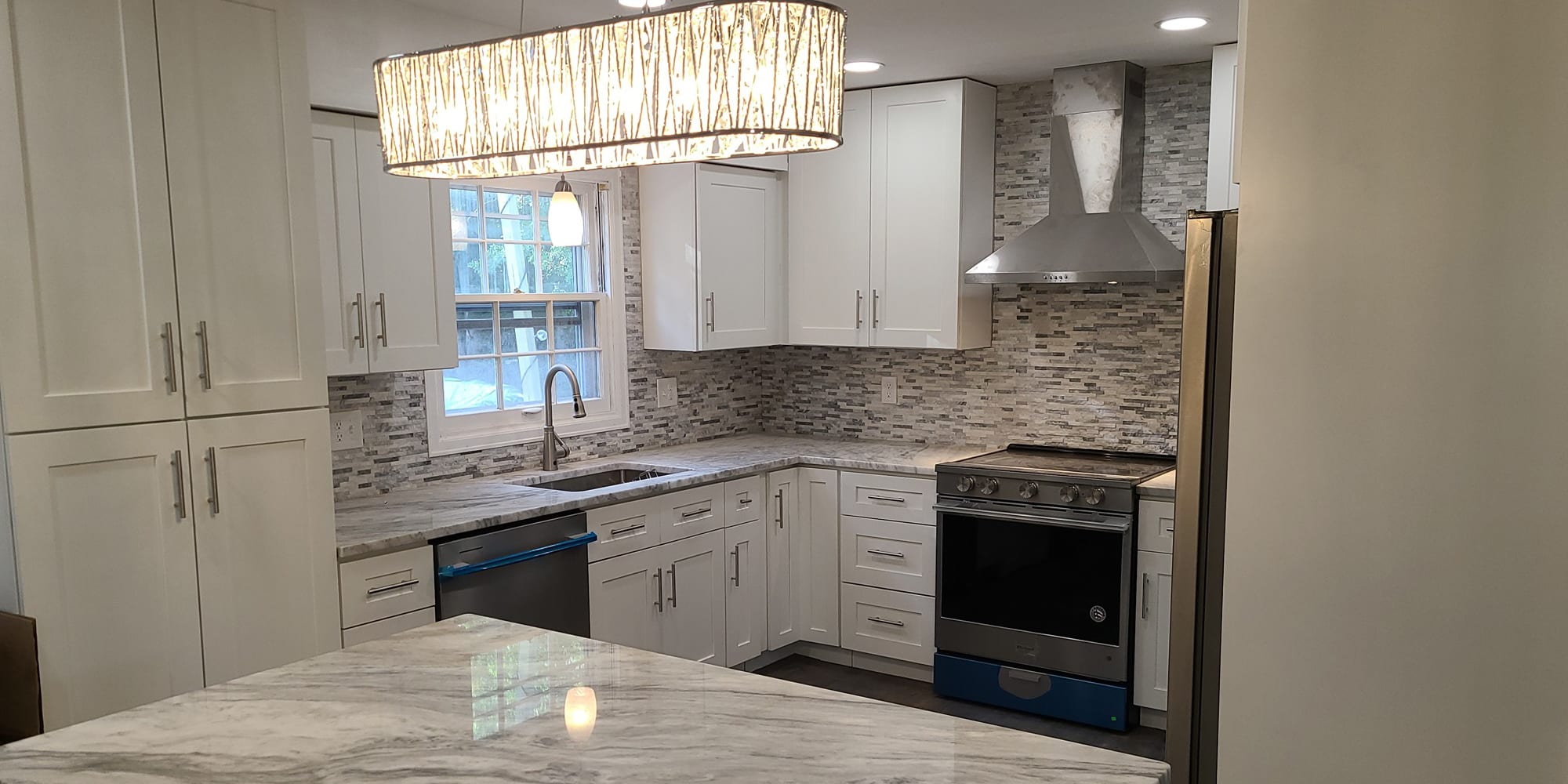 White cabinets, grey and white marble top with grey appliances with blue trim kitchen