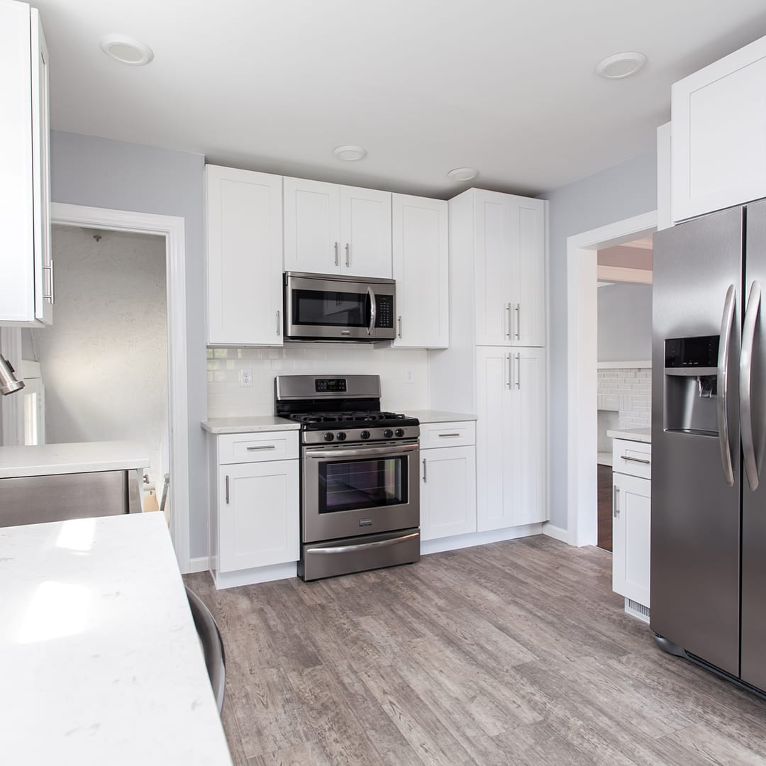 white cabinets, gray walls, and silver oven and fridge in kitchen on wooden floor