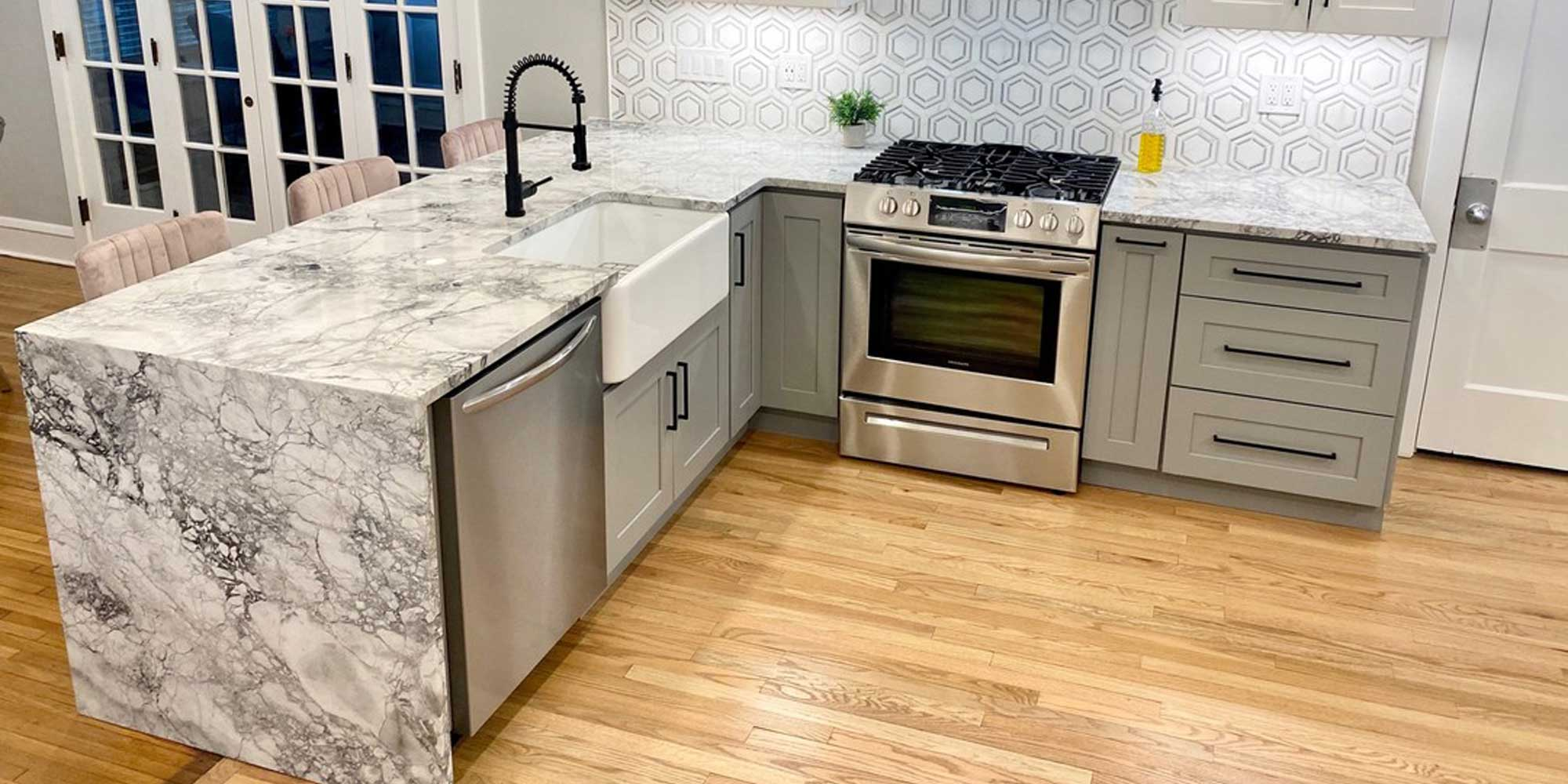 gray cabinets with silver dishwasher and stove with white sink and black faucet and marble countertop