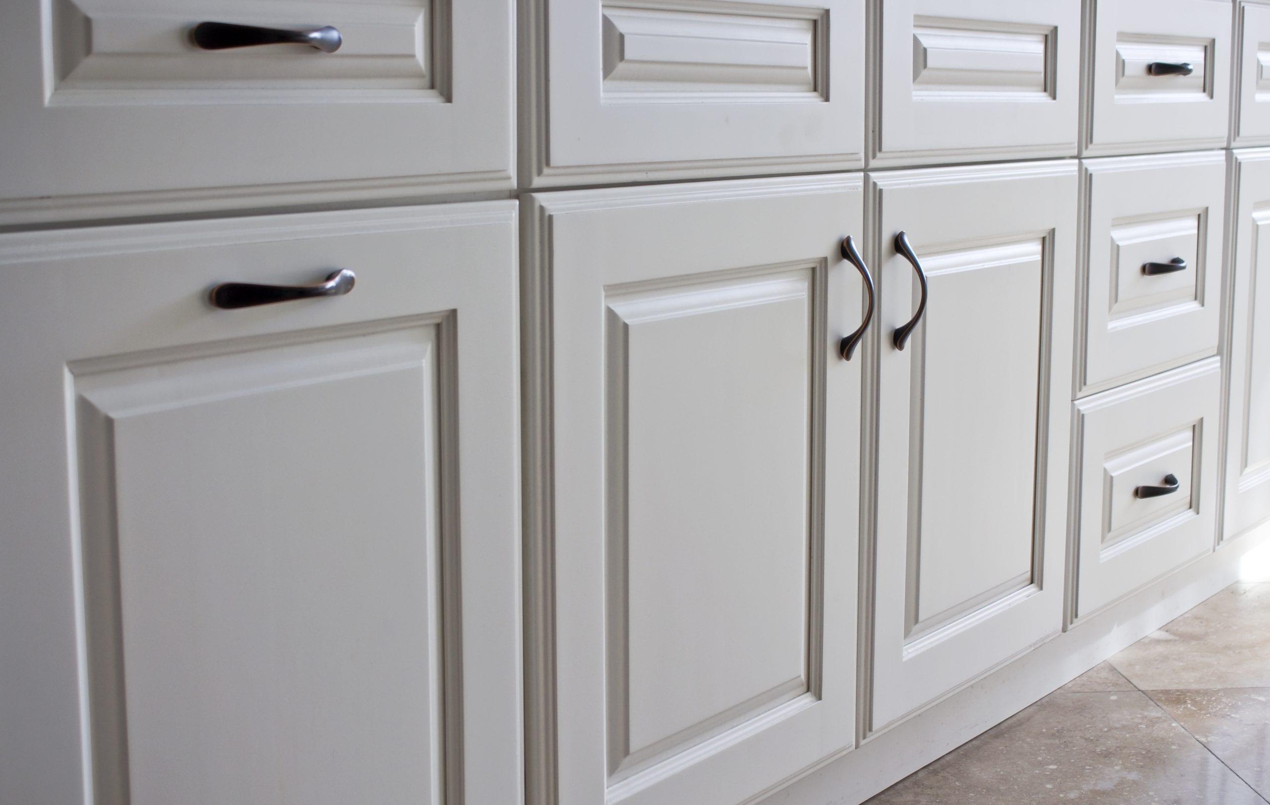 White kitchen cabinets with dark, brass fixtures.