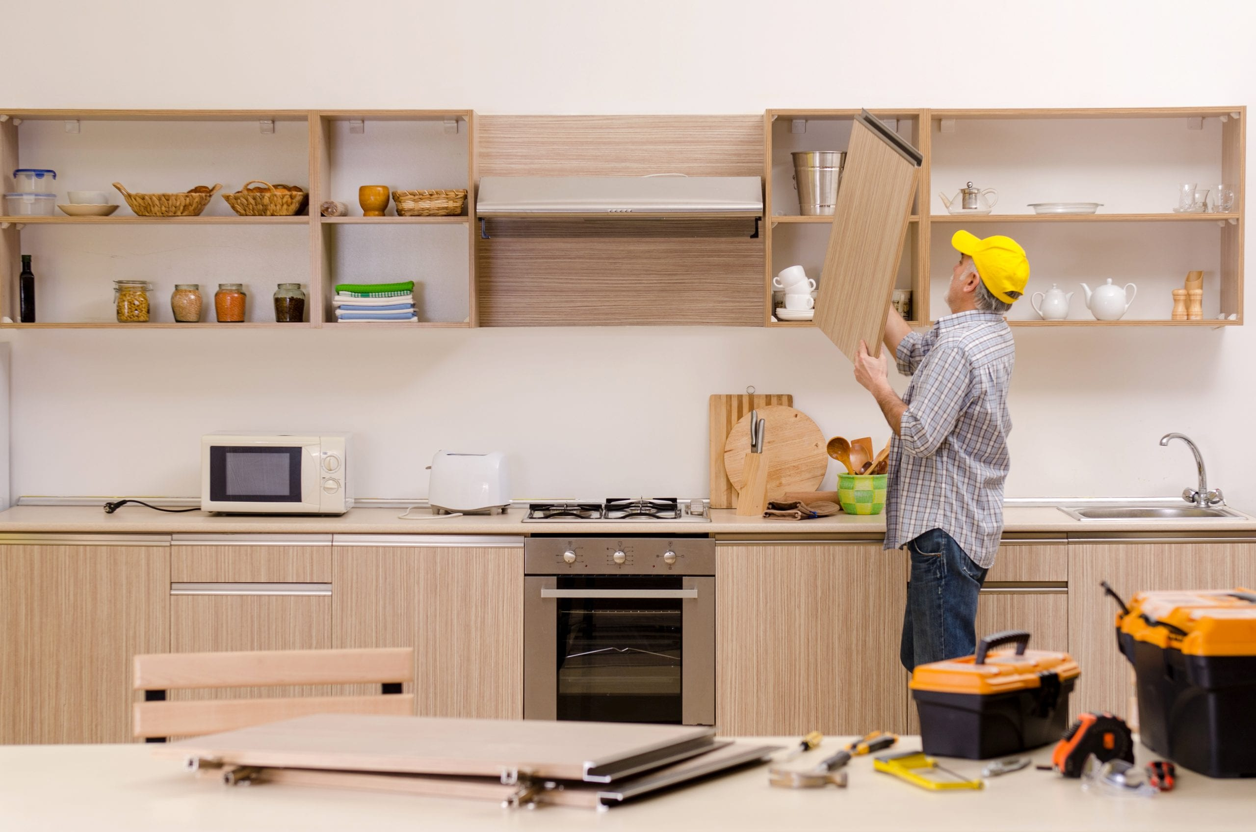 Contractor repair man working on kitchen cabinets