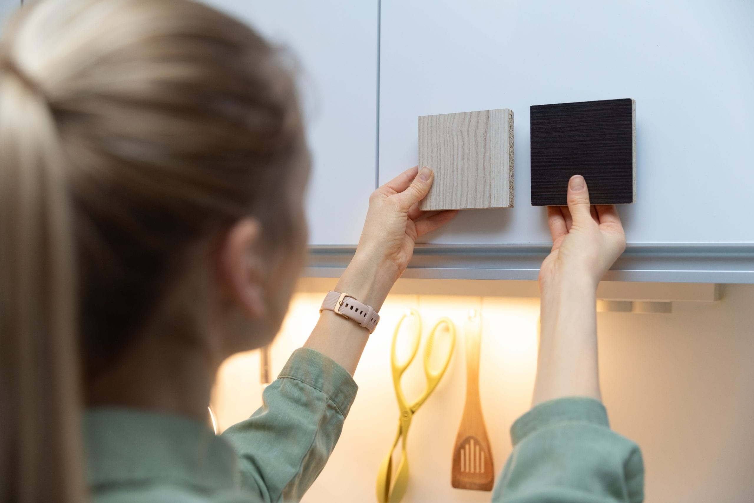 Woman choosing kitchen cabinet materials from laminate samples