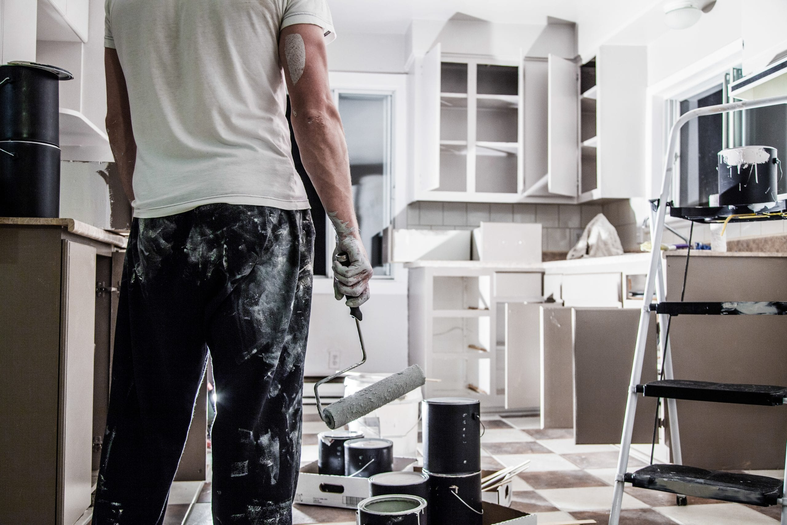 Man holding paint roller in kitchen