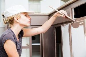 Woman painting kitchen cabinet doors