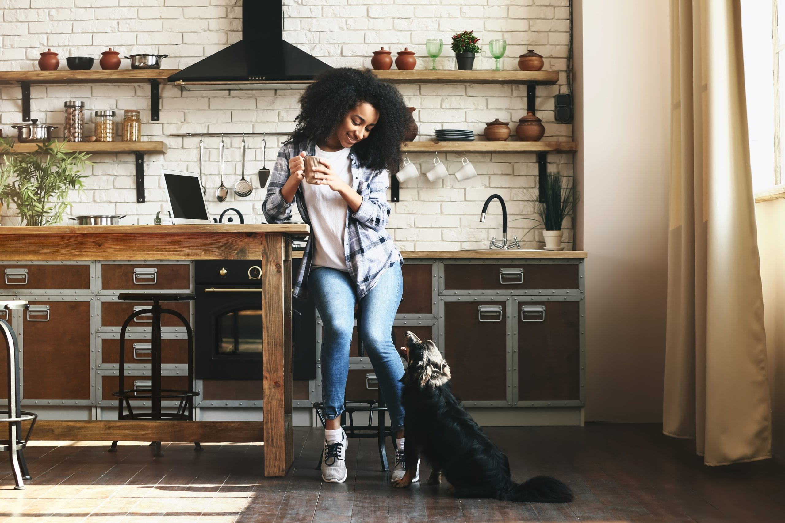 African-American woman with dark hair worn in an afro sits on a tall stool at a wooden kitchen island hold a white coffee mug, looking down at her black dog, that is looking up to her, in the back ground the kitchen has a white tile wall with open shelves, a black oven and stove vent, and brown lower cabinets with metal accents.