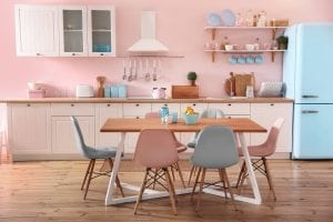 Small kitchen with pastel pinks walls, even lighter pink cabinets and oak countertops and white, blue, or pink containers and dishes, a table in the forefront with an oak top and white legs has six chairs alternating between light blue and light pink around the table, with a blue bowl of lemons in the center.