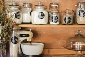 Flour, self-rising flour, caster sugar, cocoa powder, raw sugar, and pasta are displayed in glass jars with black labels with white writing on old wooden shelves, a cream colored stand mixer with a white bowl is also on the shelves.