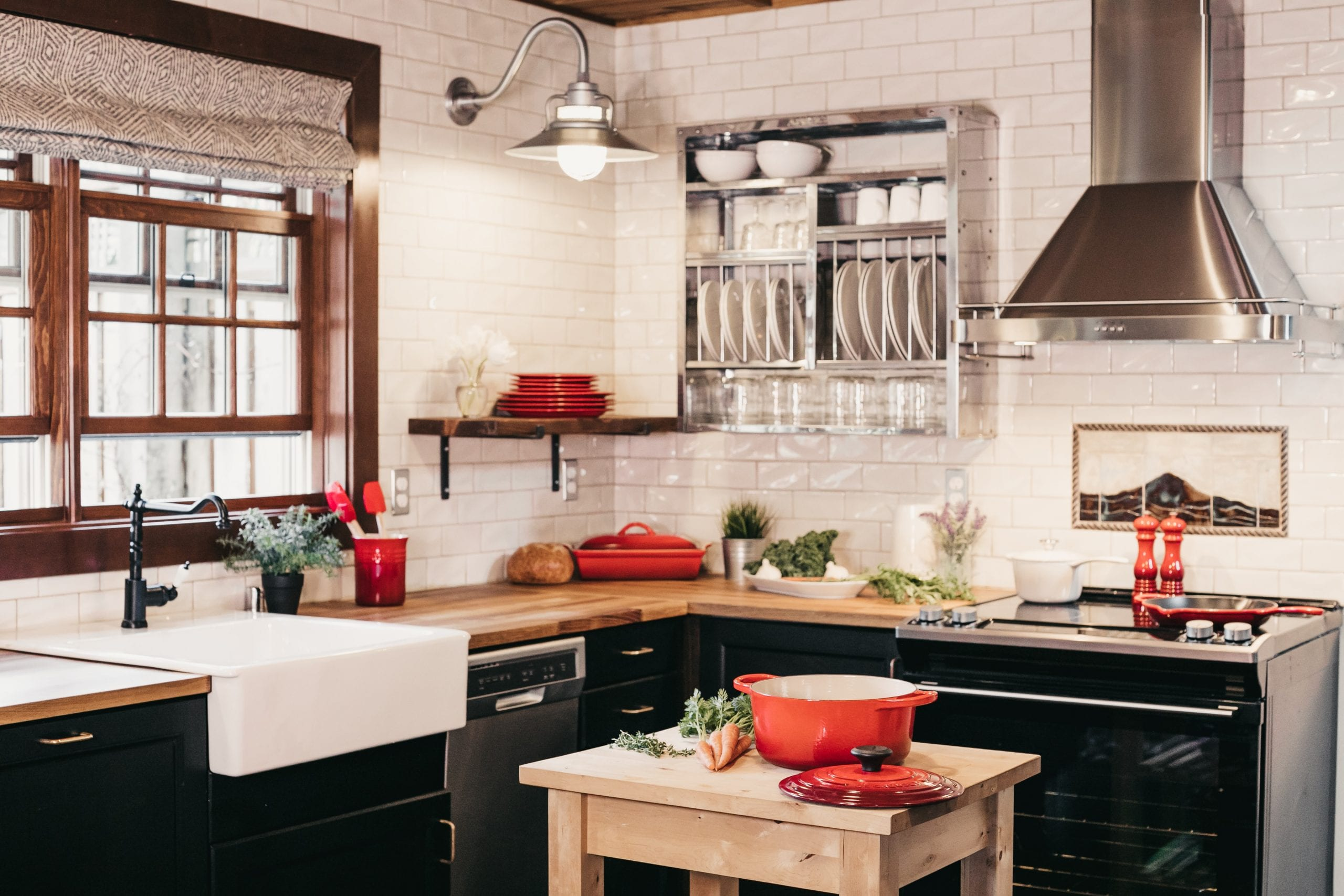 Contemporary kitchen with black cabinets, white walls, wooden countertops, and red kitchen tools