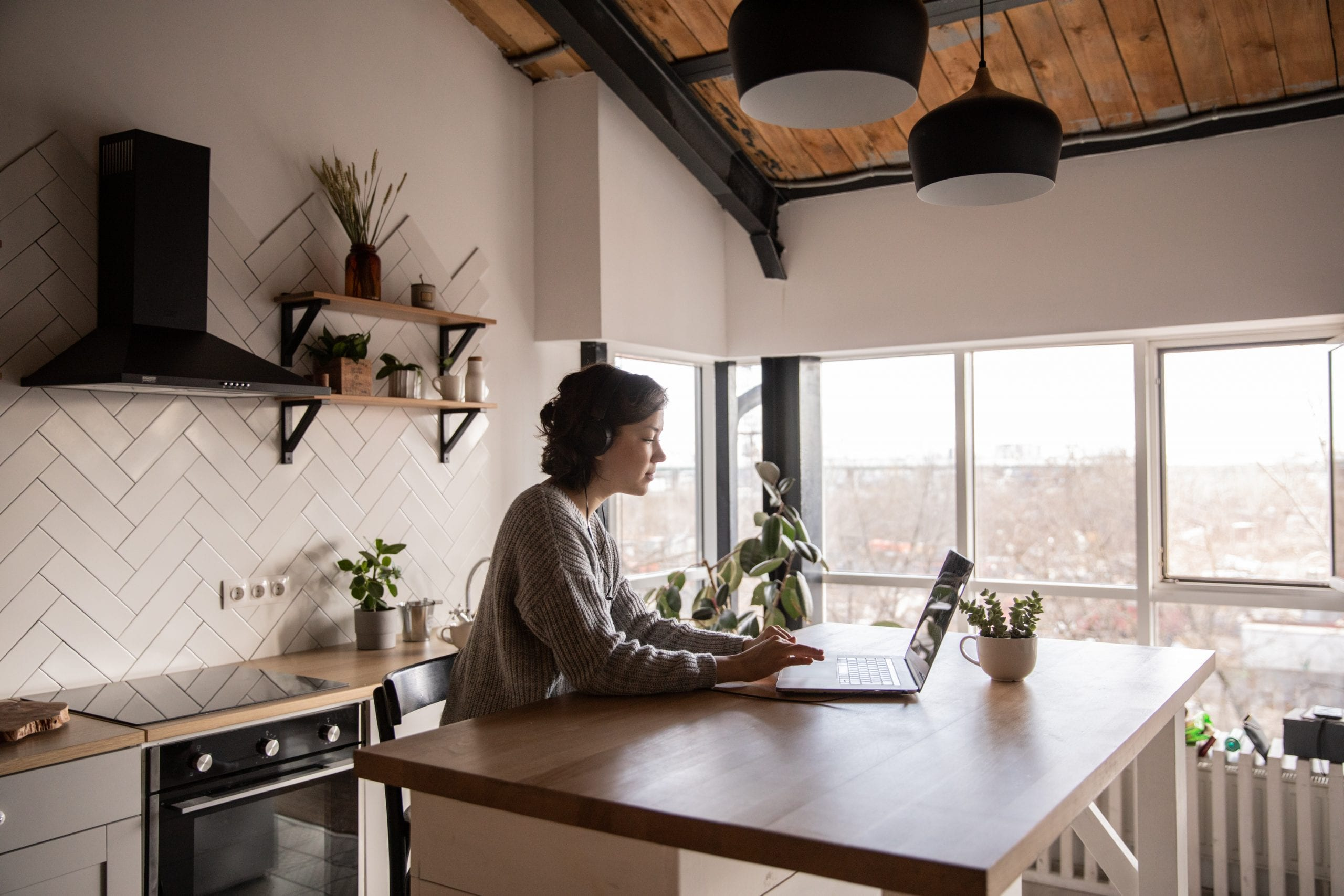 Women on her computer while sitting at her small kitchen table with stunningly gorgeous kitchen cabinet organizers, shelves and appliances are behind her.