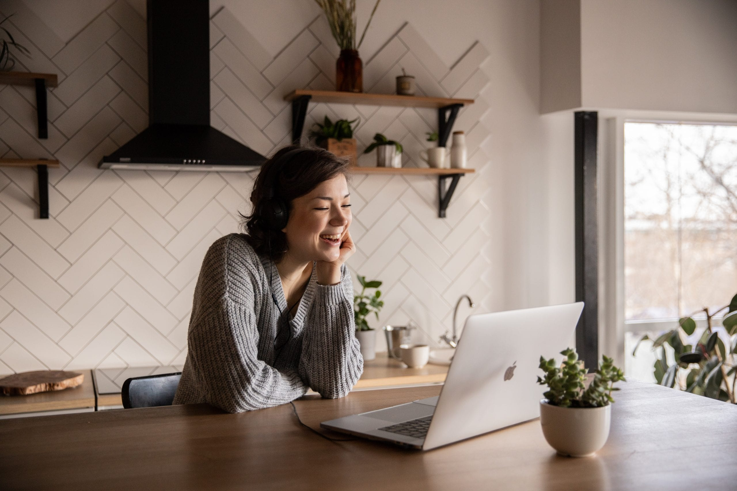 Woman working on a virtual kitchen design on her computer in her own kitchen.