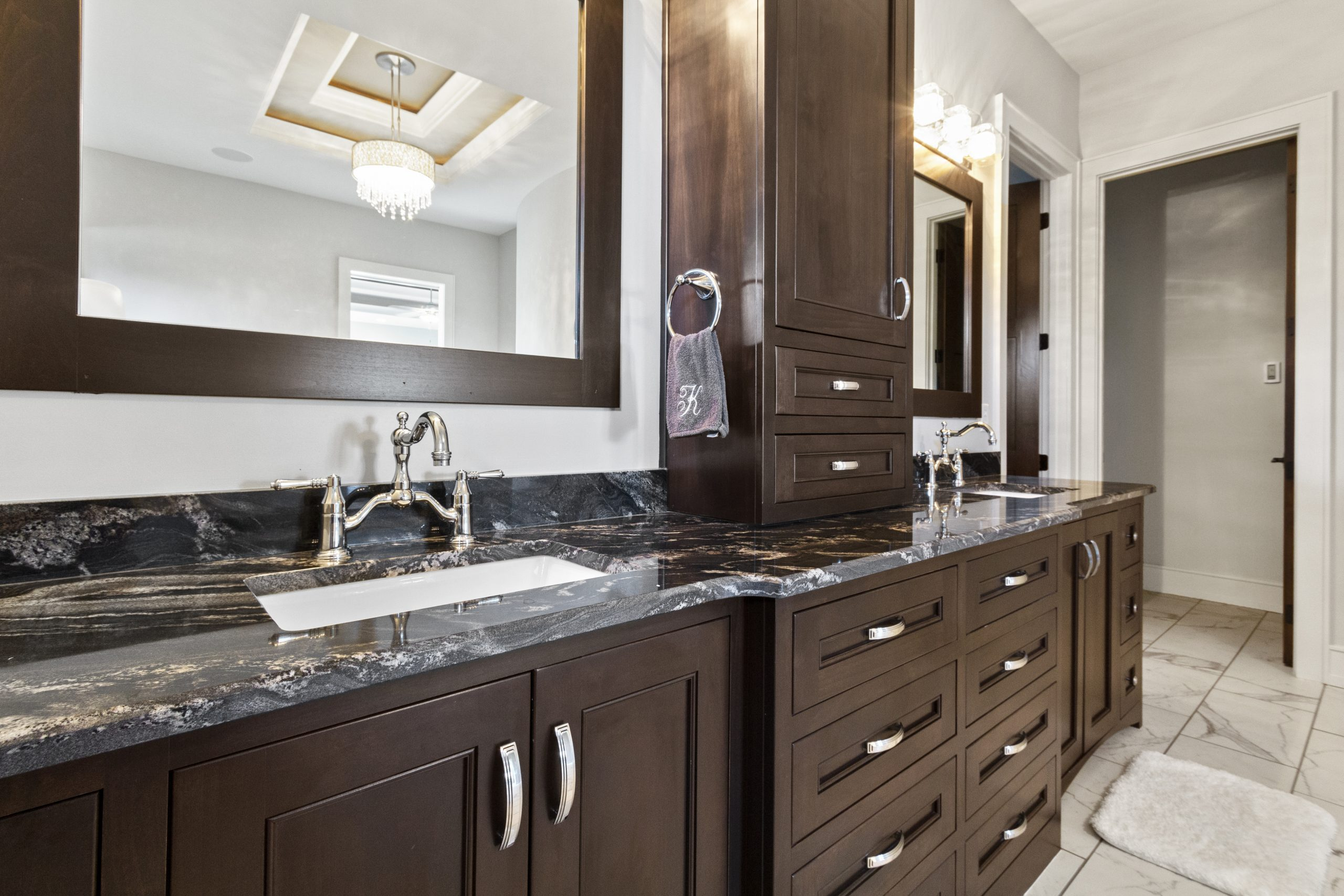 Brown cabinets in a clean master bathroom.