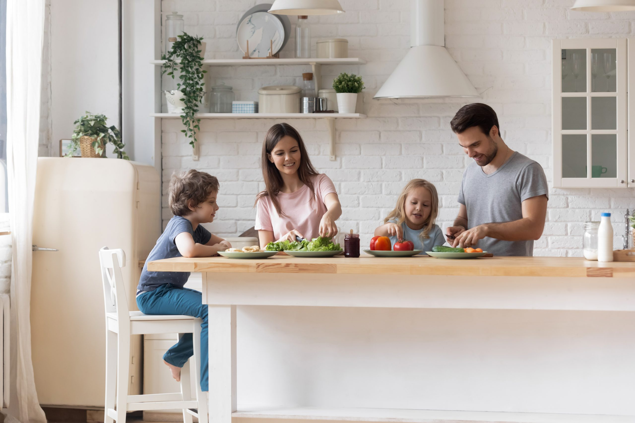 Happy parents with little children preparing salad for dinner together, standing at table at home, talking, smiling mother and father cutting vegetables in modern kitchen, family enjoying weekend