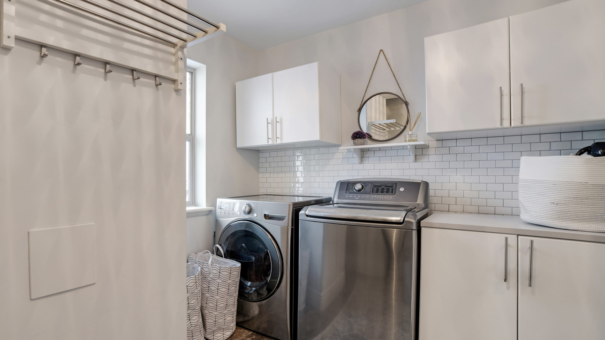 Laundry room interior with cabinets washing machine and dryer against white wall. Window, laundry basket, clothes rod, and tile floor can also be seen inside this room.