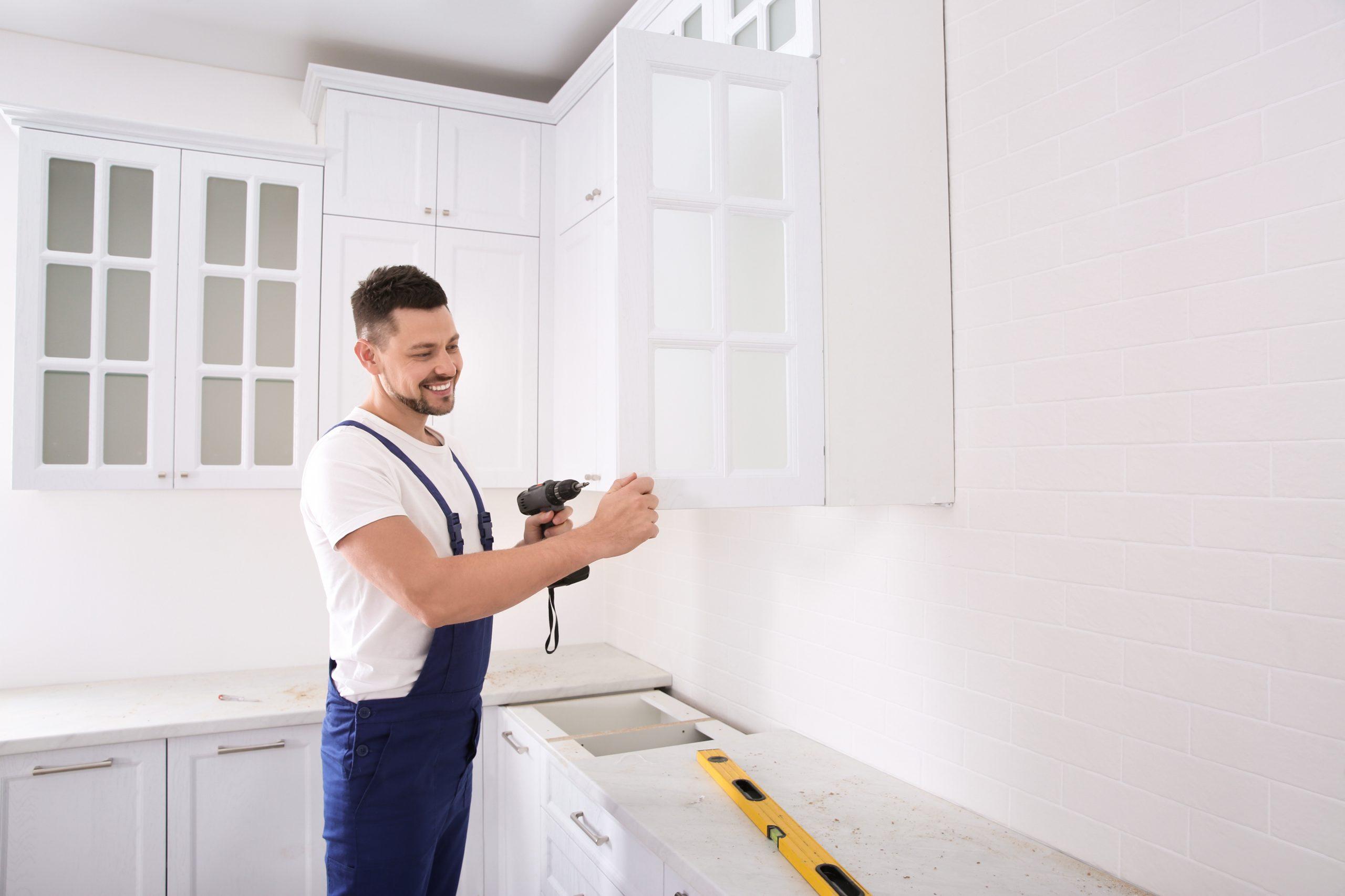 Worker installing handle on cabinet door with screw gun in kitchen