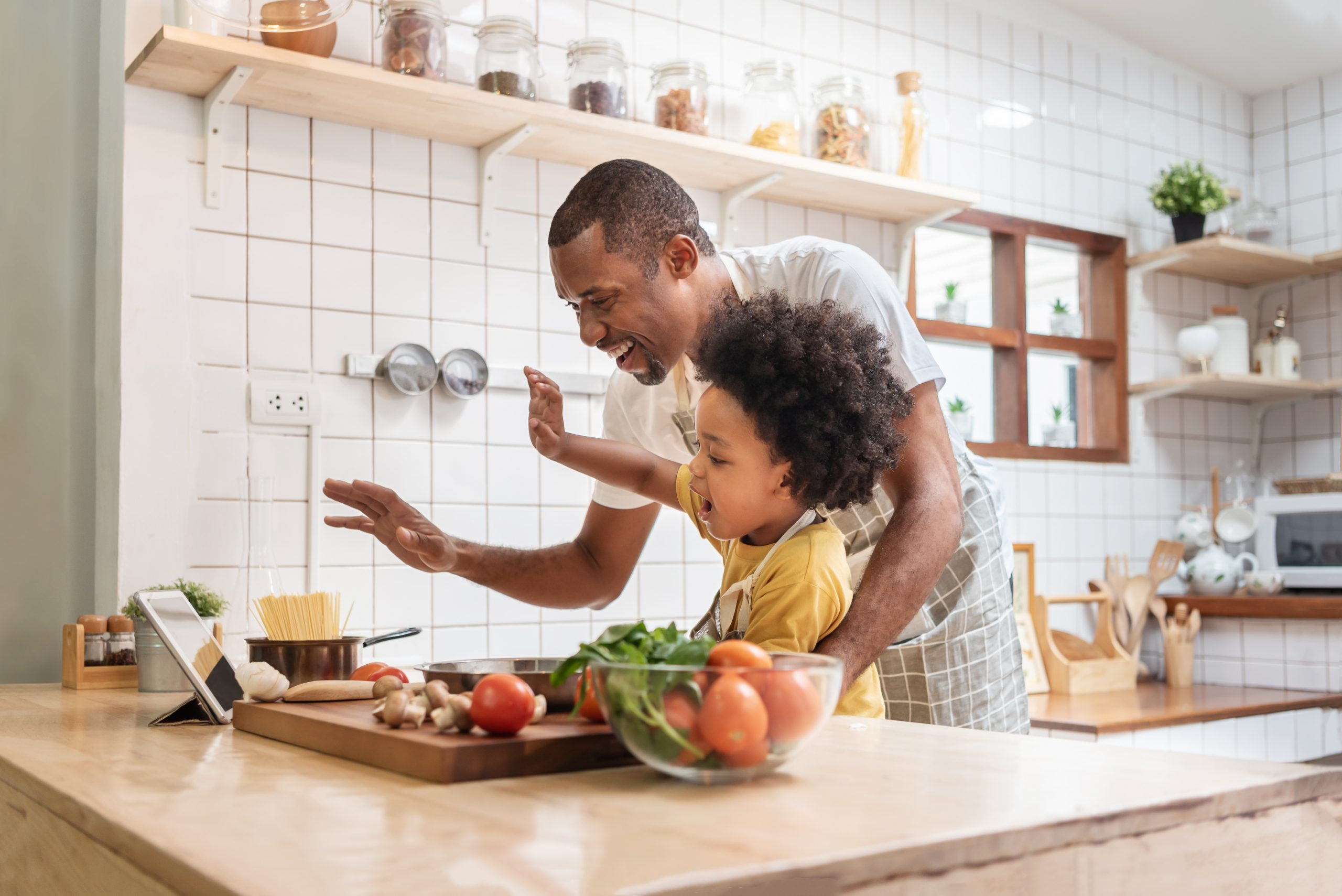 Father and little son making video call with digital tablet and waving hands laughing talking with family while cooking in kitchen