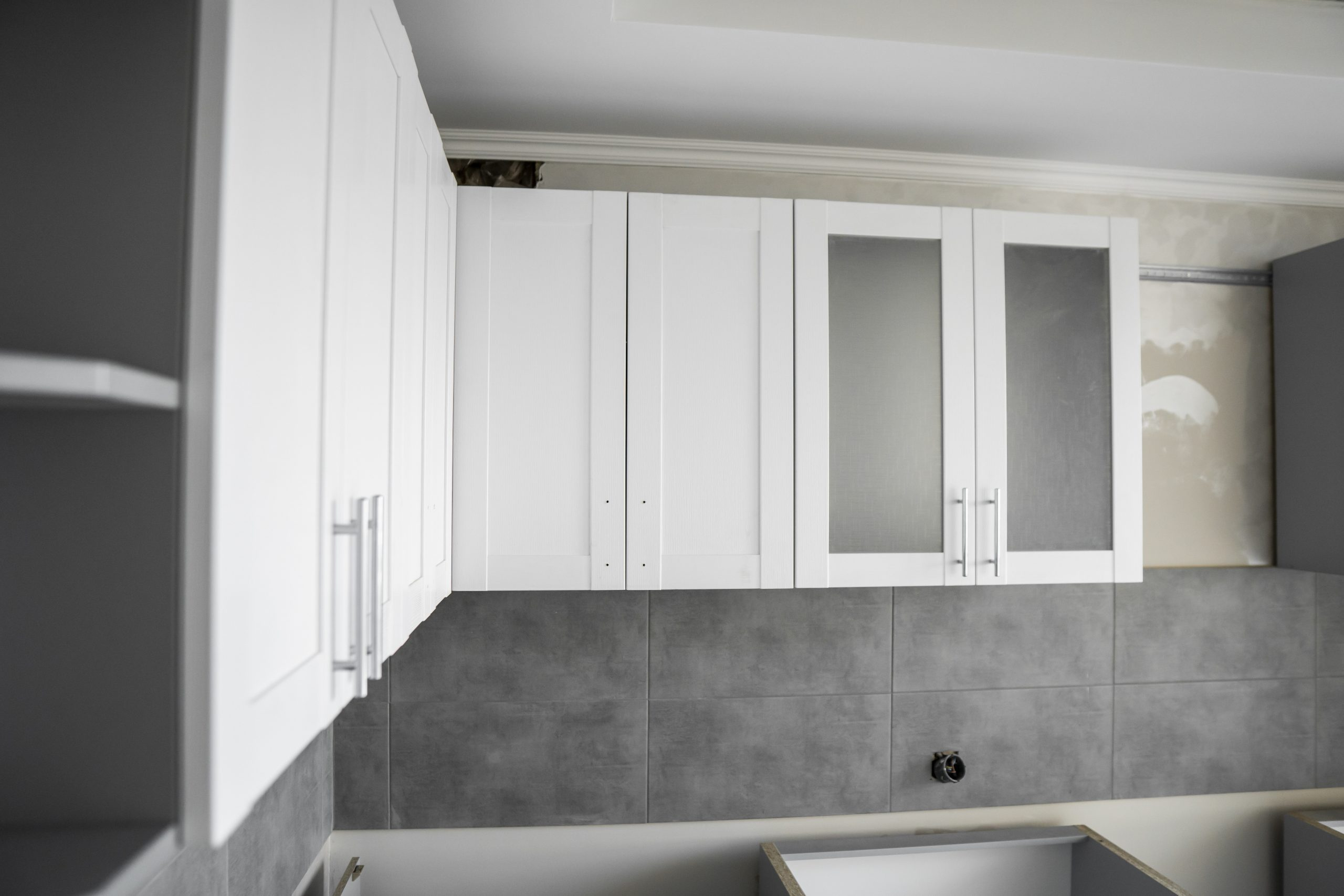 Custom kitchen cabinets installation with a white furniture, gray modular kitchen from chipboard material on a various stages of installation.